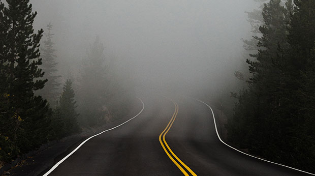 Une route disparaît dans le brouillard