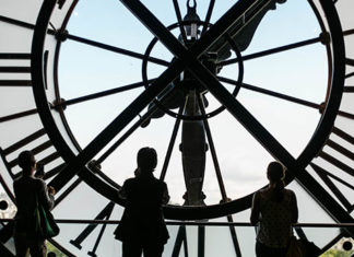 Des jeunes gens devant une horloge au musée d'Orsay