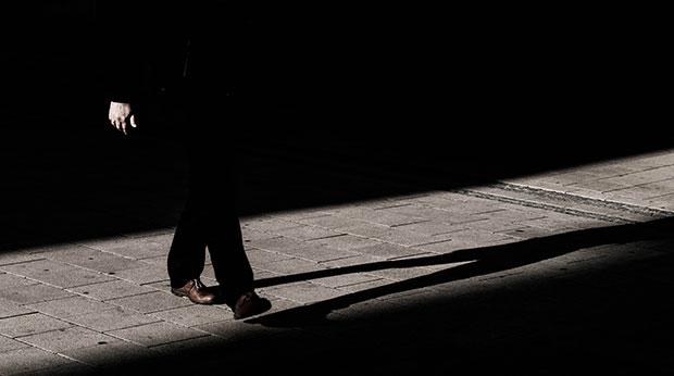 Un homme marche dans l'ombre