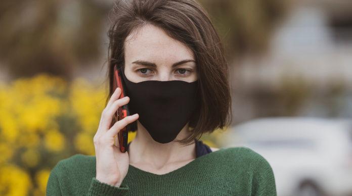 Une femme masquée au téléphone